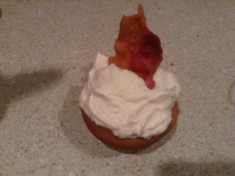 French Toast Cupcake with Maple Buttercream Frosting Garnished with a Piece of Maple Bacon
